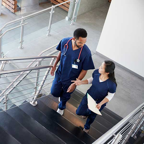 two nursing colleagues talking on a staircase
